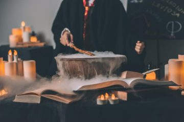 Person wearing robe and stirring potion
